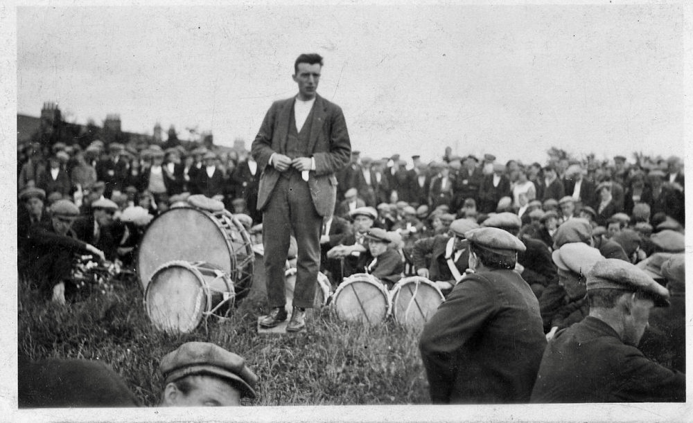 Man standing amid a crowd sitting on the grass with drums - taken from an album of photos of the 1926 general strike.