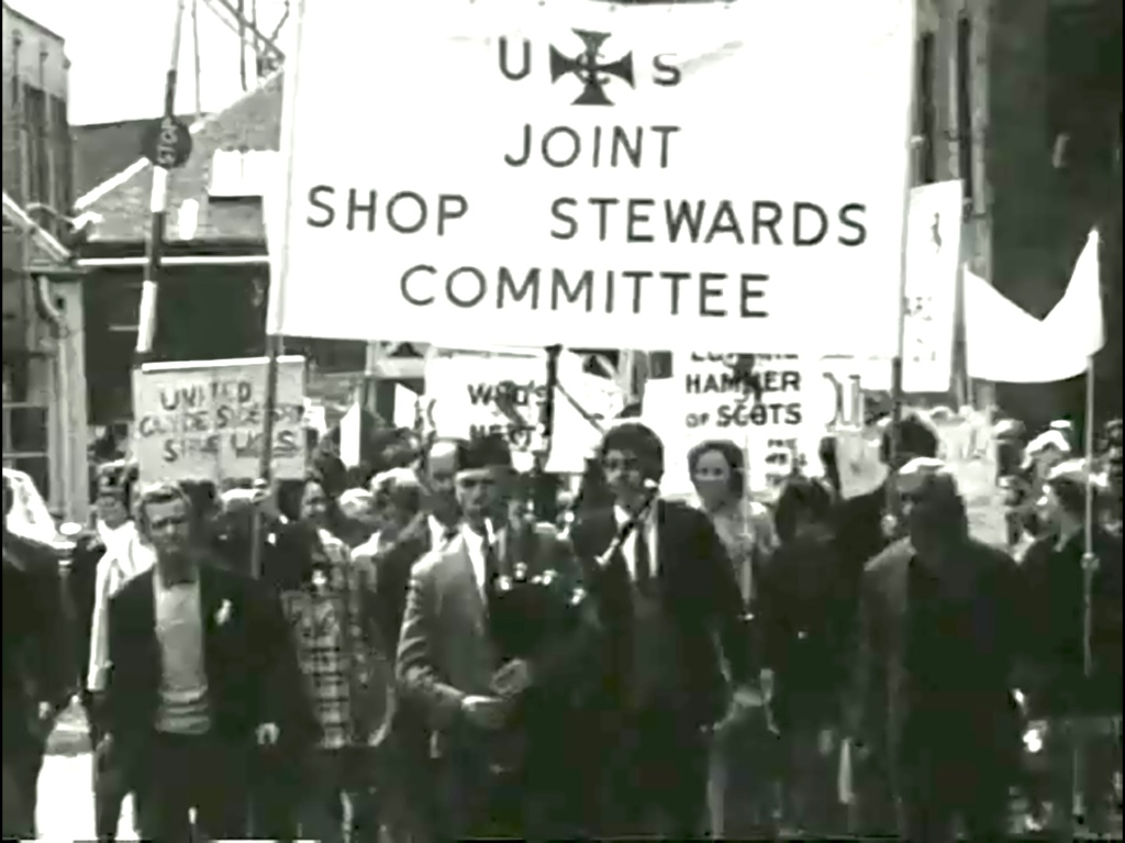 Upper Clyde Shipbuilders joint shop stewards committee lead a march out of the shipyard, headed by a piper.